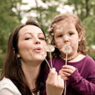 woman and girl blowing on dandelion blossom