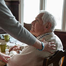 woman comforting elderly man sitting at a table