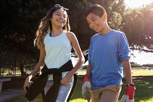 two adolescents smiling and walking
