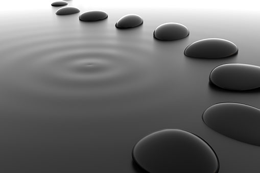 a row of stones and ripples on a pond