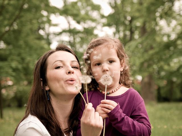 woman and child blowing on dandelion blossom