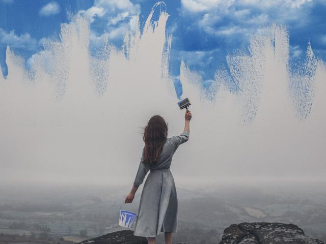 woman painting wall to look like sky